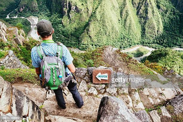 Peru, Machu Picchu region, traveler lokking at Machu Picchu citadel