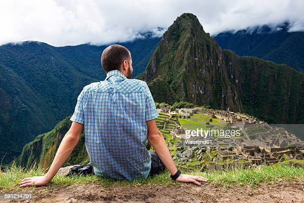 Peru, Machu Picchu region, Traveler looking at Machu Picchu citadel and Huayna mountain