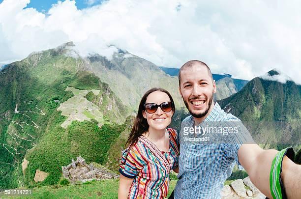 Peru, Machu Picchu region, Travelling couple taking selfie
