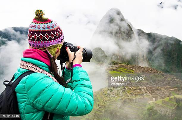 Peru, Machu Picchu region, Travelling woman taking picture of Machu Picchu Citadel
