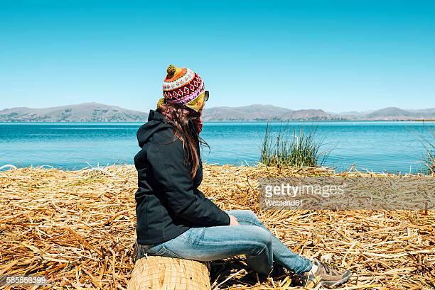 Peru, Puno, woman wearing chullo sitting on floating island in Lake Titicaca