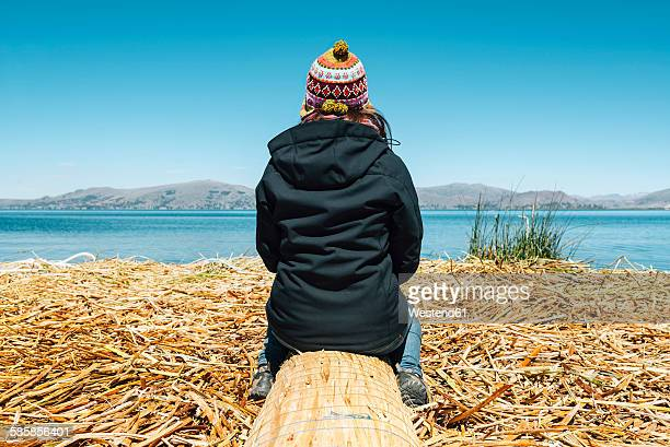 Peru, Puno, woman wearing chullo sitting on floating island in Lake Titicaca