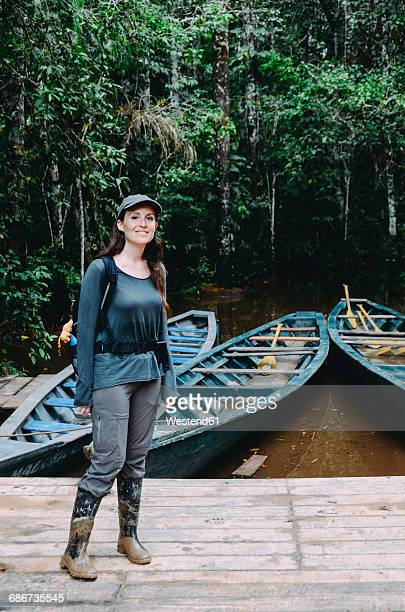 Peru, Tambopata, Woman with muddy rubber boots standing on jetty at Amazon river