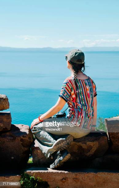 Peru, Taquile, back view of woman sitting on a rock enjoying view over Titicaca lake