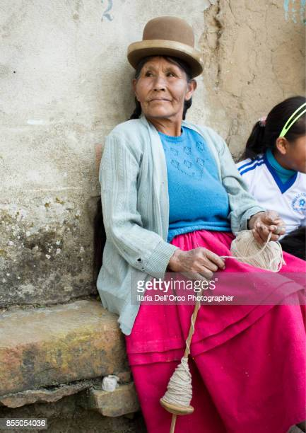 Peru, Titicaca Lake, an old woman in typical traditional Peruvian clothes, is threading the wool