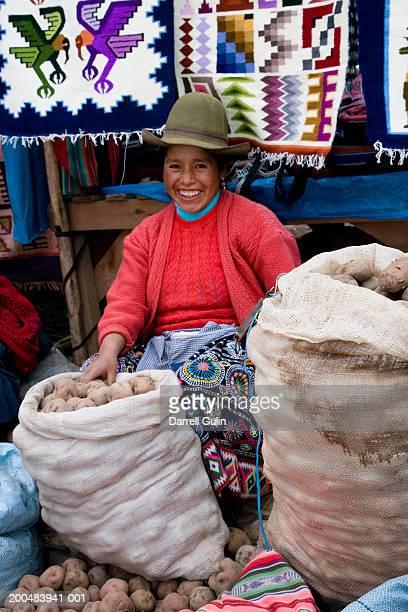 Peru, Urubamba Valley, woman selling potatoes at Pisac Market
