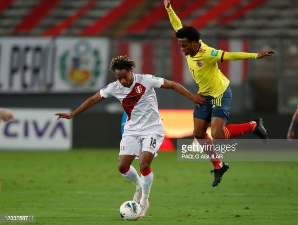 Peru's Andre Carrillo and Colombia's Juan Guillermo Cuadrado vie for the ball during their South American qualification football match for the FIFA...