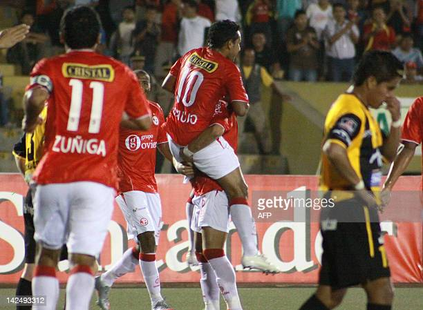 Peru's Aurich Alfredo Rojas lifts Javier Araújo celebrating the latter's goal against Bolivia Strongest during the eliminatory game played at the...
