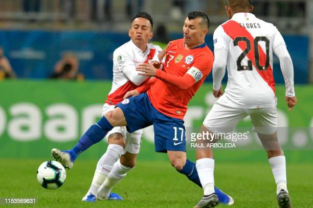 Peru's Christian Cueva and Chile's Gary Medel vie for the ball during their Copa America football tournament semifinal match at the Gremio Arena in...