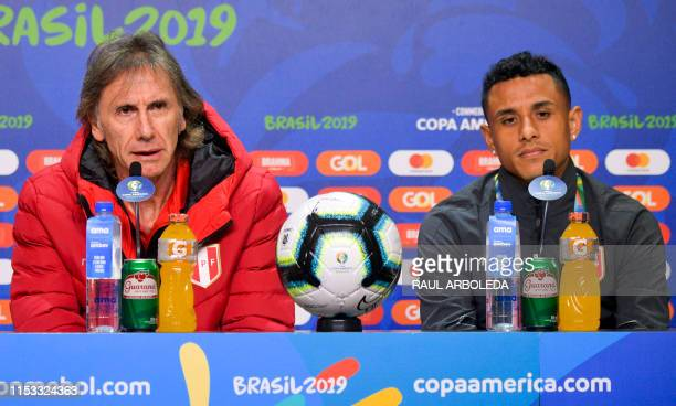 Peru's coach Ricardo Gareca speaks next to player Yoshimar Yotun during a press conference in Porto Alegre Brazil on July 2 on the eve of their Copa...