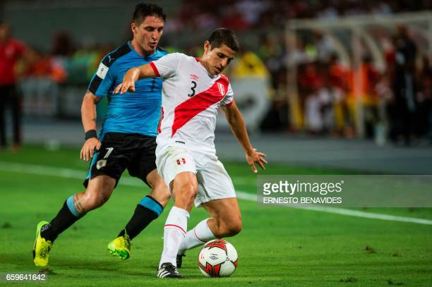 Peru's defender Aldo Corzo and Uruguay's Cristian Rodriguez vie for the ball during the 2018 FIFA World Cup qualifier football match in Lima on March...