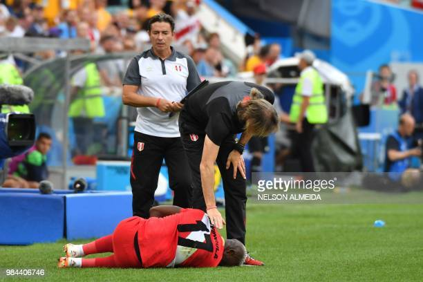 Peru's defender Luis Advincula is checked on by Peru's coach Ricardo Gareca during the Russia 2018 World Cup Group C football match between Australia...