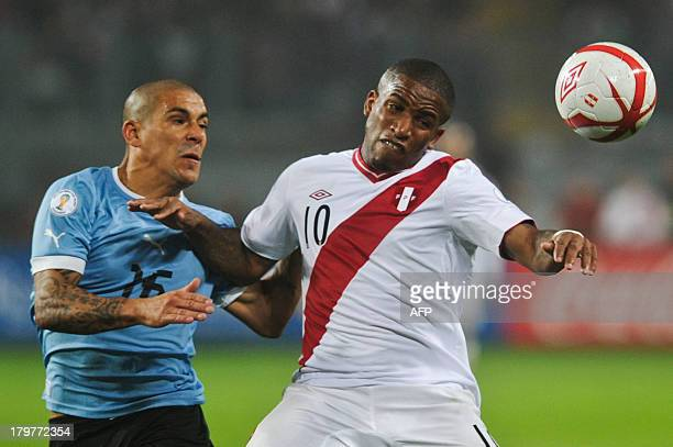 Peru's footballer Jefferson Farfan and Uruguay's Maximiliano Pereira vie during the FIFA Brazil 2014 World Cup South American qualifier match in Lima...