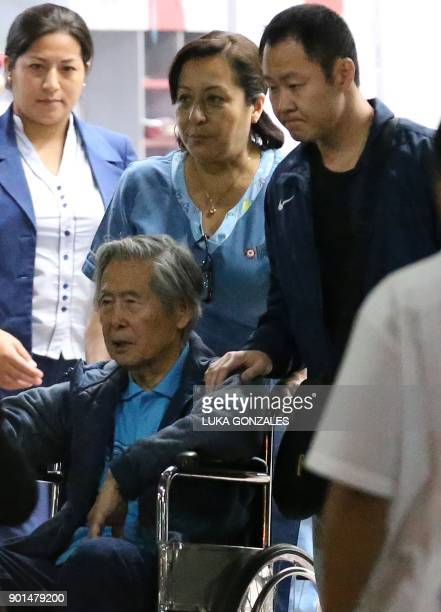 Peru's former President Alberto Fujimori is wheeled out of the Centenario Clinic with his son Congressman Kenji Fujimori in Lima on January 04 where...