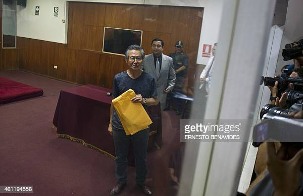 Peru's former President Alberto Fujimori poses for the press before the reading of the verdict on charges of embezzling state funds and using them to...