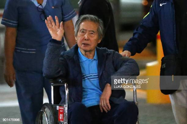 Peru's former President Alberto Fujimori waves to supporters as he is wheeled out of the Centenario Clinic in Lima on January 04 where he was...