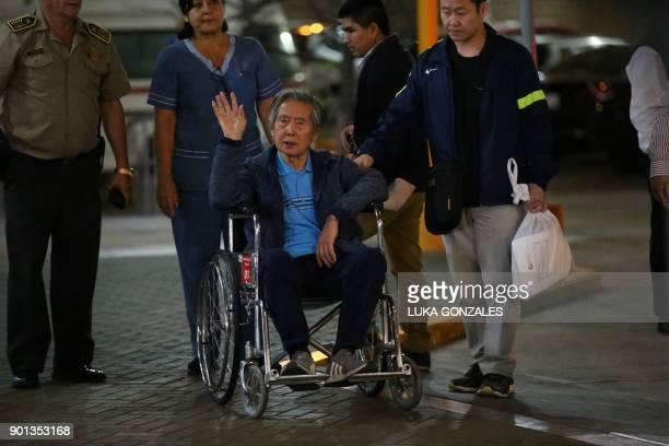 Peru's former President Alberto Fujimori waves to supporters beside his son Congressman Kenji Fujimori as he is wheeled out of the Centenario Clinic...