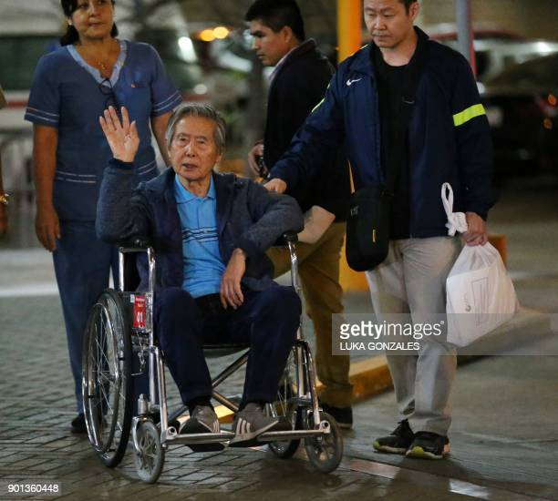 Peru's former President Alberto Fujimori waves to supporters beside his son Congressman Kenji Fujimori as he is wheeled out of the Centenario Clinic...