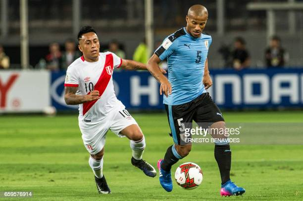 Peru's forward Christian Cueva and Uruguay's Carlos Sanchez vie for the ball during the 2018 FIFA World Cup qualifier football match in Lima on March...