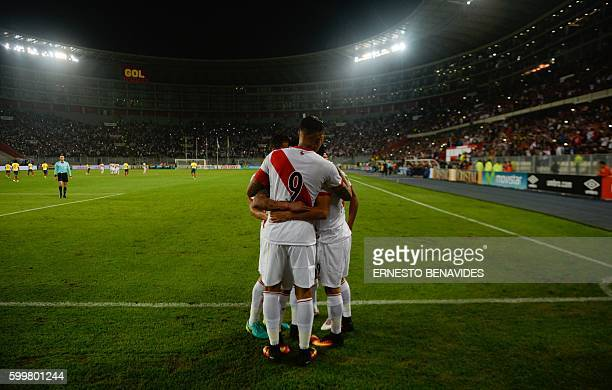 Peru's forward Christian Cueva celebrates with teammate Paolo Guerrero and other players after scoring against Ecuador during their Russia 2018 World...