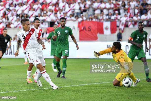 Peru's forward Paolo Guerrero scores his team's second goal past Saudi Arabia's goalkeeper Abdullah AlMayouf during an international friendly...