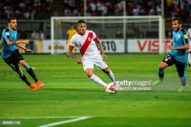 Peru's forward Paolo Guerrero vies for the ball with Uruguay's Matias Vecino and Uruguay's Alvaro Gonzalez during their 2018 FIFA World Cup qualifier...