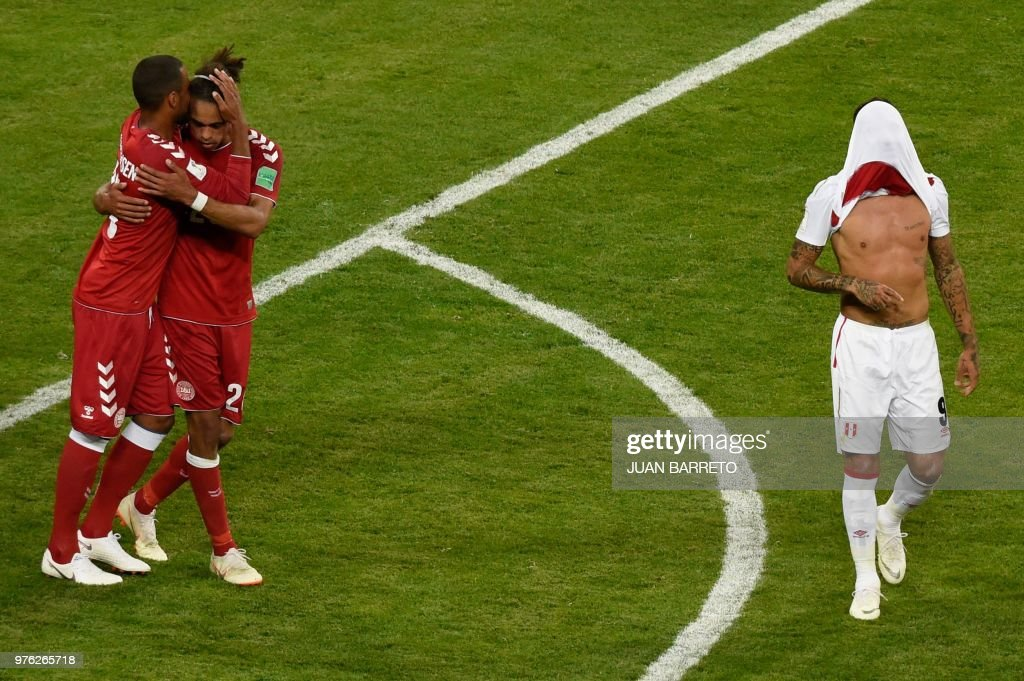 TOPSHOT - Peru's forward Paolo Guerrero (R) walks with his shirt over his face as Denmark's forward Yussuf Poulsen (2L) and Denmark's forward Nicolai Jorgensen (L) react after the final whistle during the Russia 2018 World Cup Group C football match between Peru and Denmark at the Mordovia Arena in Saransk on June 16, 2018. (Photo by JUAN BARRETO / AFP) / RESTRICTED