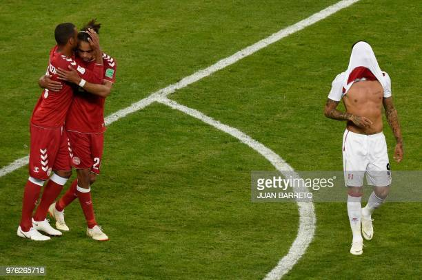 TOPSHOT Peru's forward Paolo Guerrero walks with his shirt over his face as Denmark's forward Yussuf Poulsen and Denmark's forward Nicolai Jorgensen...
