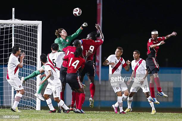 Peru's goalkeeper Diego Penny clears the ball hounded by Trinidad Tobago players during their friendly match at Ato Bolton stadium in Couva Trinidad...