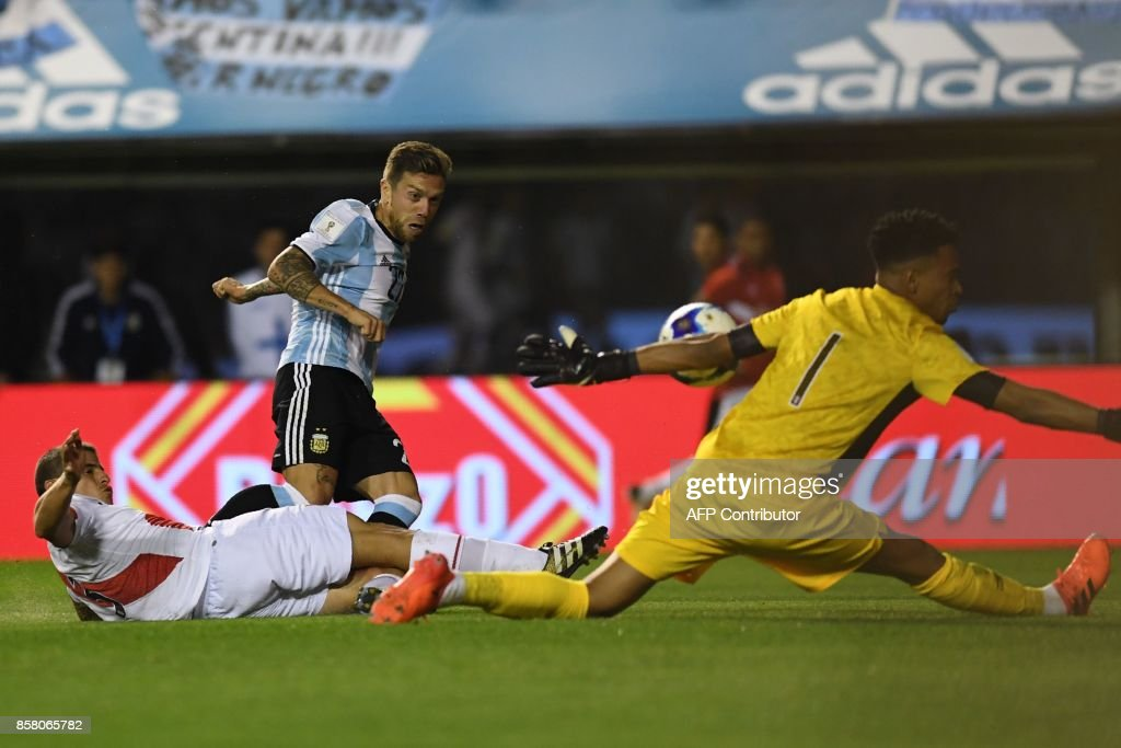 Peru's goalkeeper Pedro Gallese stops a shot by Argentina's Alejandro Gomez (C) during their 2018 World Cup qualifier football match in Buenos Aires on October 5, 2017. / AFP PHOTO / Eitan ABRAMOVICH