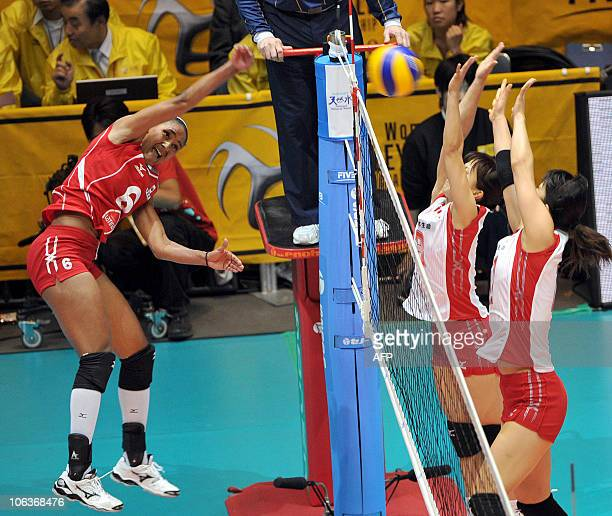 Peru's Jessenia Uceda spikes the ball against Japan's Hitomi Nakamichi and Erika Araki during the 1st round of the world woman's volleyball...
