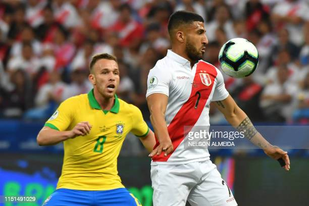 Peru's Josepmir Ballon and Brazil's Arthur vie for the ball during their Copa America football tournament group match at the Corinthians Arena in Sao...