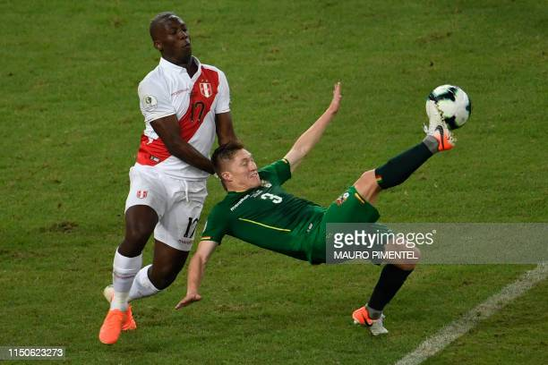 TOPSHOT Peru's Luis Advincula and Bolivia's Alejandro Chumacero vie for the ball during their Copa America football tournament group match at...