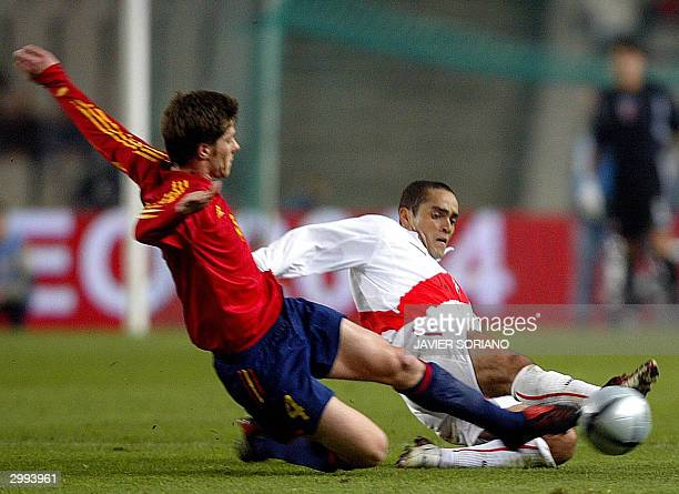 Peru's Marko Ciurlizza tackles Spain's Xavi Alonso during their friendly match at the Olympic Lluis Companys stadium in Barcelona 18 February 2004...