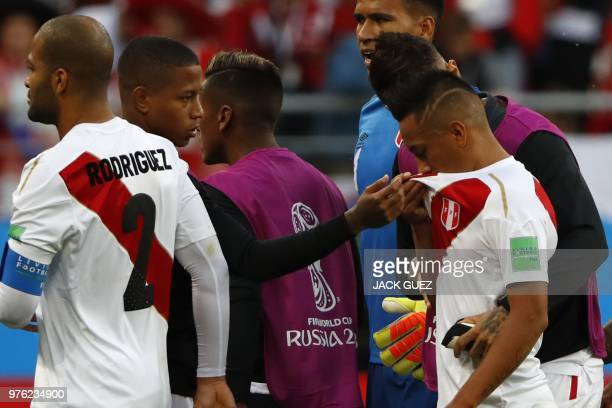 TOPSHOT Peru's midfielder Christian Cueva is consoled by his teammates after failing his penalty kick during the Russia 2018 World Cup Group C...