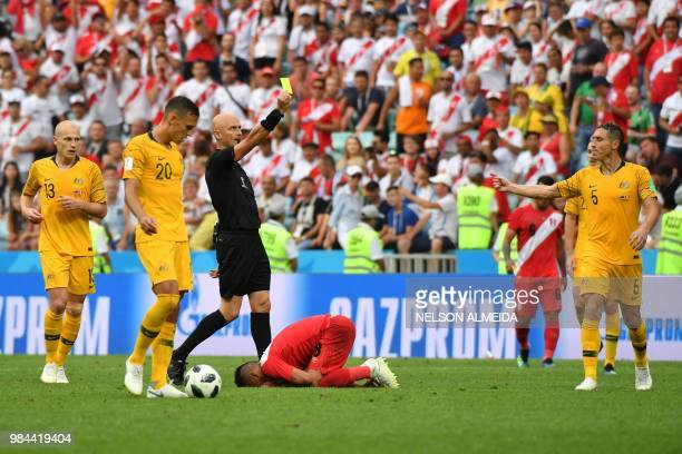 Peru's midfielder Christian Cueva reacts as Australia's defender Mark Milligan receives a yellow card from Russian referee Sergei Karasev during the...