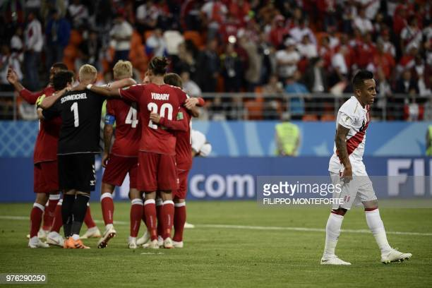 Peru's midfielder Christian Cueva reacts next to Denmark's football players celebrating after winning at the end of the Russia 2018 World Cup Group C...