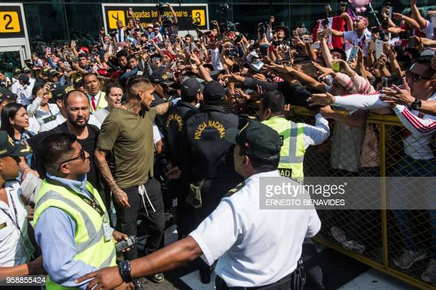 Peru's national football team captain Paolo Guerrero is greeted by supporters as he arrives at the Jorge Chavez airport in Lima on May 15 2018 a day...