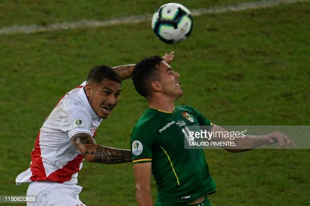 Peru's Paolo Guerrero and Bolivia's Luis Haquin jump for the ball during their Copa America football tournament group match at Maracana Stadium in...