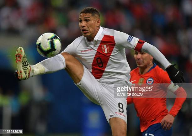 Peru's Paolo Guerrero controls the ball over Chile's Gary Medel during their Copa America football tournament semifinal match at the Gremio Arena in...