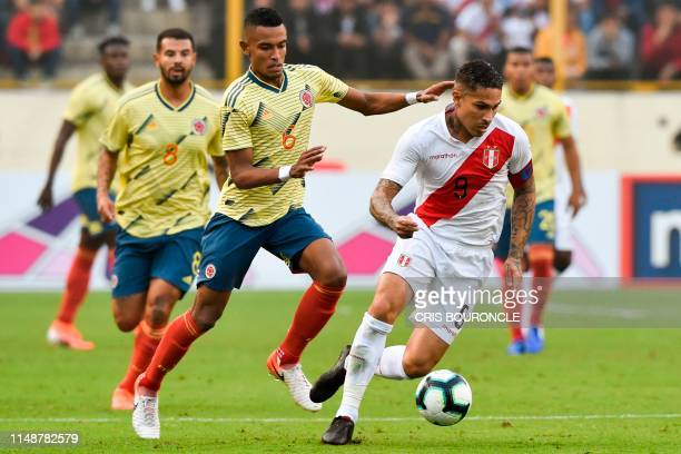 Peru's Paolo Guerrero is chased by Colombia's William Tesillo during a friendly football match between Peru and Colombia at the Monumental Stadium in...