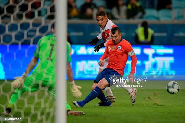 Peru's Paolo Guerrero is marked by Chile's Gary Medel uring their Copa America football tournament semifinal match at the Gremio Arena in Porto...