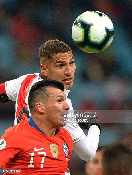 Peru's Paolo Guerrero vies for the ball with Chile's Gary Medel during their Copa America football tournament semifinal match at the Gremio Arena in...