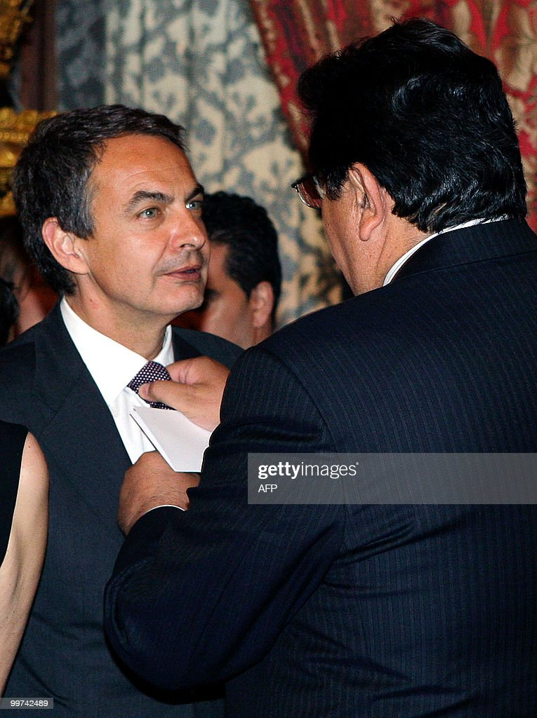 Peru's President Alan Garcia (R) adjusts Spanish Prime Minister Jose Luis Rodriguez Zapatero' s tie during a gala dinner at The Royal Palace in Madrid on May 17, 2010. European and Latin America heads of states meet in Madrid from 17 to 19 May, 2010 during an European Union-Latin America and Caribean countries summit organized by the Spanish rotating presidency of the EU.