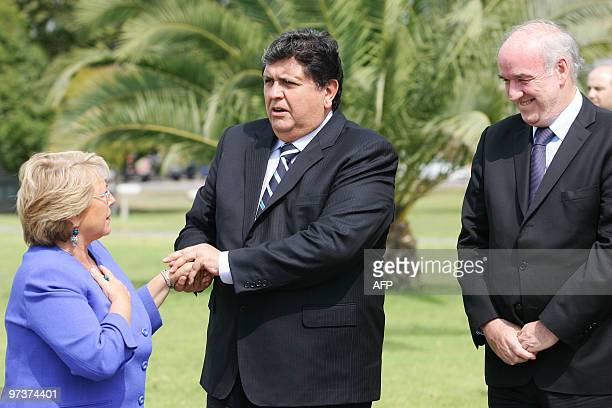 Peru's President Alan Garcia talks to his Chilean counterpart Michelle Bachelet upon his arrival in Santiago next to Peru's Foreign Minister Jose...