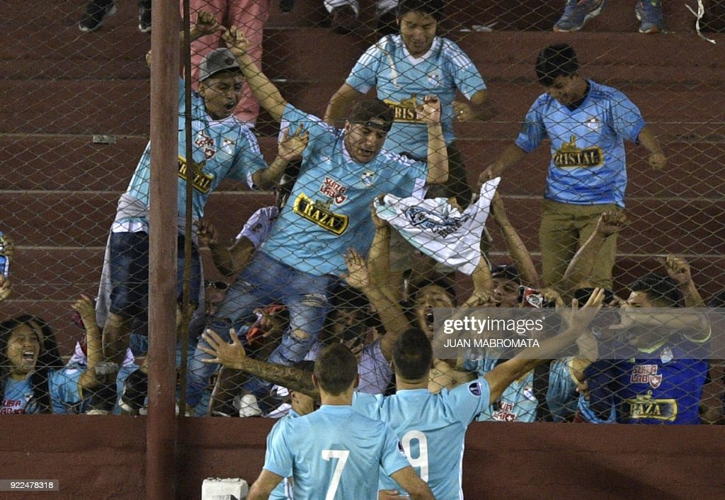 Peru's Sporting Cristal forward Emanuel Herrera (R) celebrates with teammates and suporters after scoring the team's second goal against Argentina's Lanus during the Copa Sudamericana 2018 first stage football match at 'La Fortaleza' stadium in Lanus, Buenos Aires, Argentina, on February 21, 2018. /