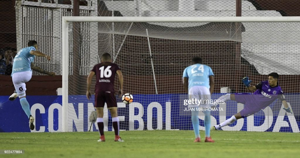 Peru's Sporting Cristal forward Emanuel Herrera (L) scores by penalty kick the team's second goal against Argentina's Lanus goalkeeper Esteban Andrada (R) during their Copa Sudamericana 2018 first ...