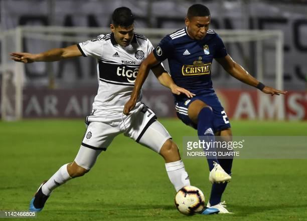 Peru's Sporting Cristal player Fernando Pacheco vies for the ball with Paraguay's Olimpia Colombian Jorge Arias during their Copa Libertadores...