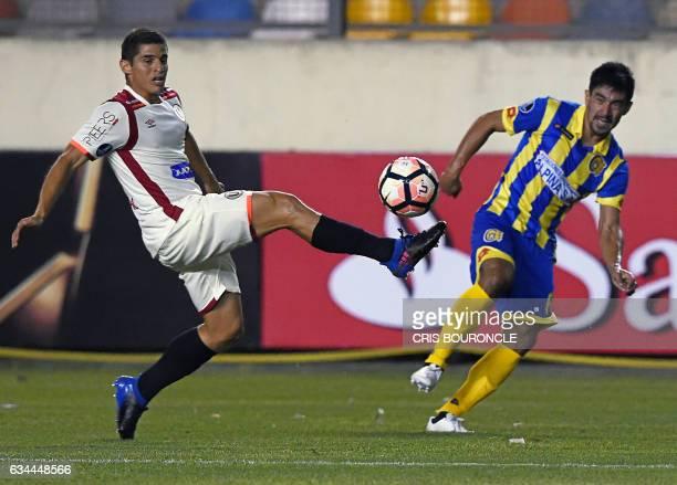 Perus Universitario player Aldo Corzo and Paraguays Deportivo Capiata player Cristian Martinez vie for the ball in the firstround Copa Libertadores...