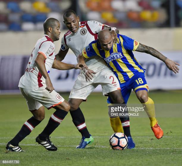 Perus Universitario players Alberto Rodriguez and John Galliquio vie for the ball with Paraguays Deportivo Capiata player Dioniso Perez Mambreani...